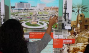 A viewer goes through the images uploaded at the installation 'Sanduq El-Dunia', Copenhagen, Denmark (Photo: Ati Metwaly)