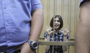Nadezhda Tolokonnikova, a member of female punk band, ''Pussy Riot'', gestures as she sits behind bars during a court hearing in Moscow June 20, 2012. (Photo: Reuters)