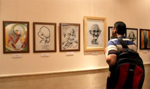 "A visitor looks at the row of caricatures, part of ""Spirit of Gandhi in Egypt"" exhibition that opened in Maulana Azad Centre for Indian Culture on 2 October 2013. (Photo: Ati Metwaly)"